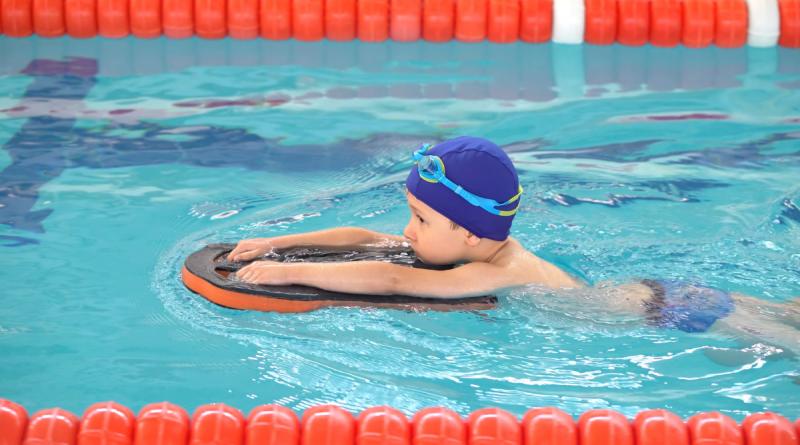 chłopiec w czerwonym czepku pływający w basenie