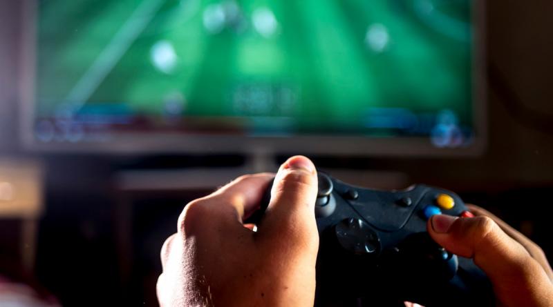 dłonie obsługujące jojstik na pierwszsym planie, w tle ekran komputera